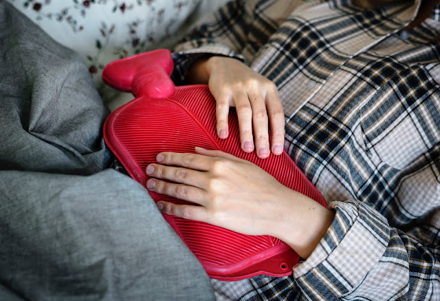 The middle section of a woman in PJs, under a blanket with a hot water bottle