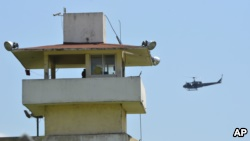 A police helicopter flies over the state prison in Acapulco, Mexico, July 6, 2017.