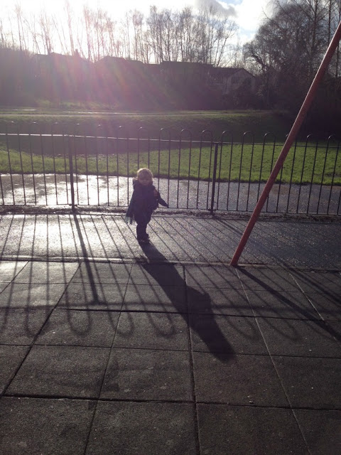 Toddler with sun behind him in park, casting shadows