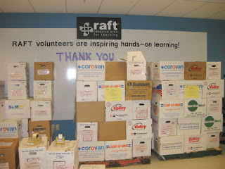 "Cartons of the kits we prepared, stacked on pallets, in front of a sign that reads ""RAFT volunteers are inspiring hands-on learning! Thank you"", Resource Area for Teachers, Sunnyvale, California"