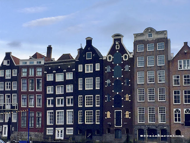 Houses in Damrak avenue, in Amsterdam