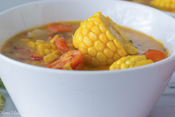 a piece of corn on top of a bowl of corn soup