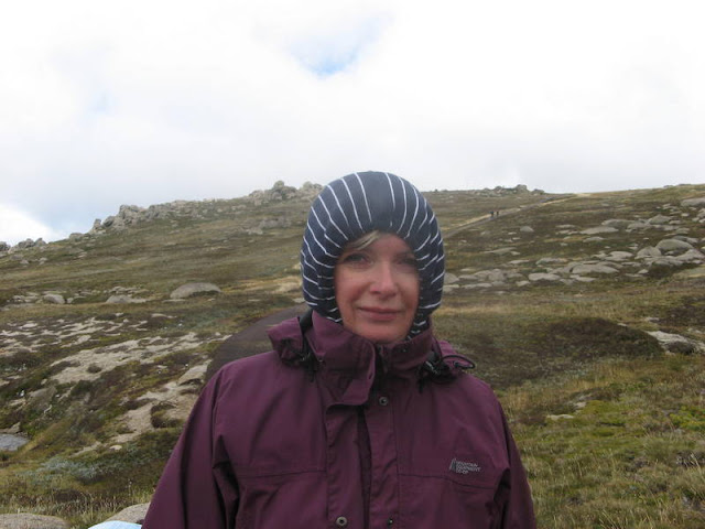 woman on a mountainside, with hood drawn tightly over her head, looking cold
