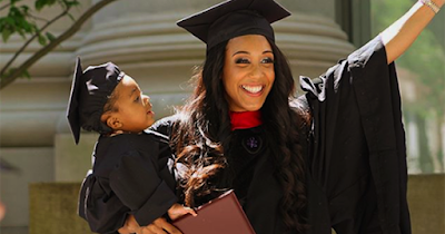 African American mother holding her child at her college graduation