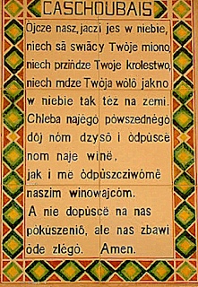 The Lord's Prayer in Kashubian, in black text on a tan background, with yellow, green, and red geometric designs in the margins.