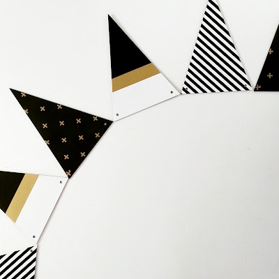 Set of triangular wooden bunting in black, white and gold patterns.