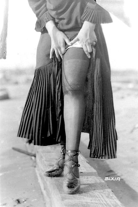 photograph around 1900, a woman showing her stockinged leg