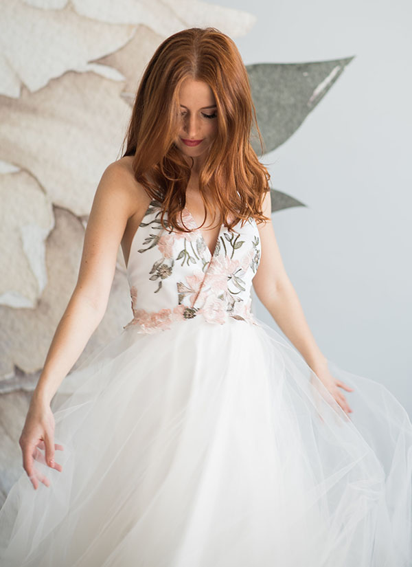 This beautiful a-line wedding dress has a full tulle skirt and floral embroidered bodice. It is one of many affordable wedding dresses from She Wore Flowers.
