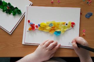 Um aluno assina o seu trabalho: uma sardinha coberta com escamas de peixe de várias cores.