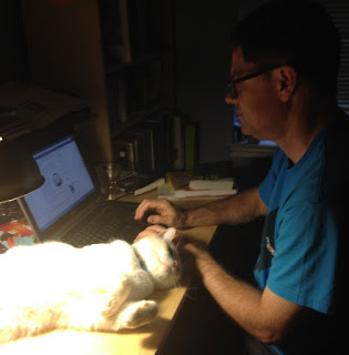 David working on his blog with Charlie the Cat lounging nearby