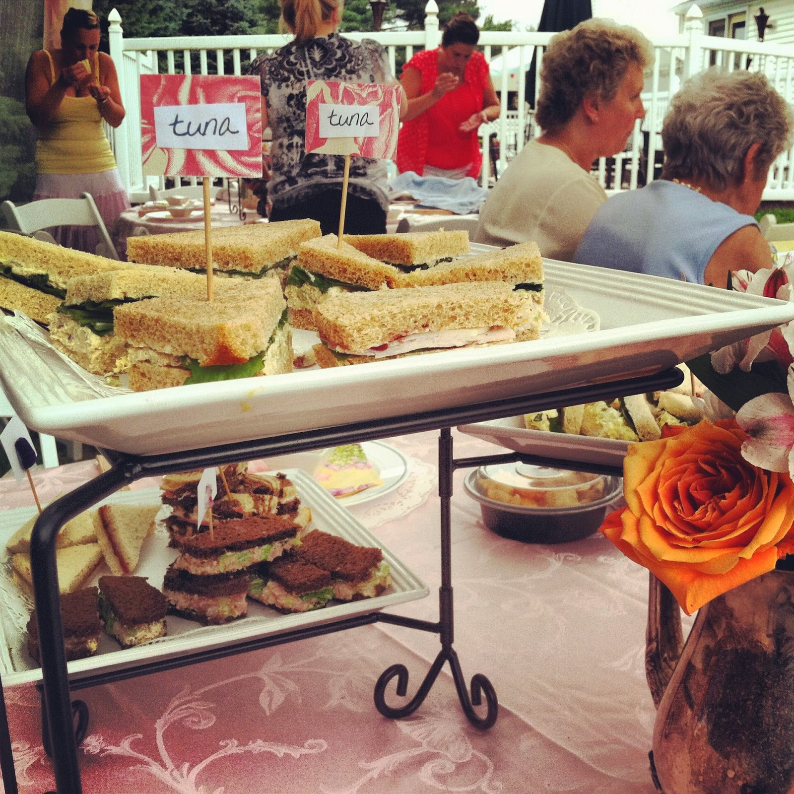 tea sandwiches with little labels served on tiered trays for an afternoon lunch