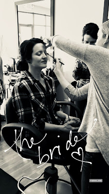 Photo of a bride getting her makeup done before her wedding.