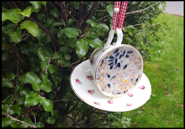 Hanging tea cup bird feeders in the garden for the winter months