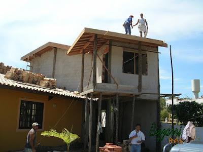 Execução do madeiramento já pronto com o forro de madeira por cima dos caibros e na marquise do terraço os pilares de madeira de eucalipto tratado com toda a laje da parte superior apoiada em vigas de madeira nos pilares de madeira.