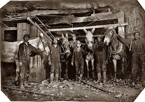 Hooded mules and miners pose in Library of Congress 1908 image.