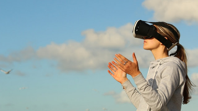 Seorang perempuan sedang bermain virtual reality di bawah langit biru