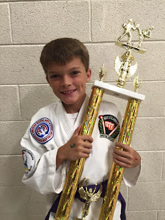 A purple belt martial arts karate kid holding 1st place trophy