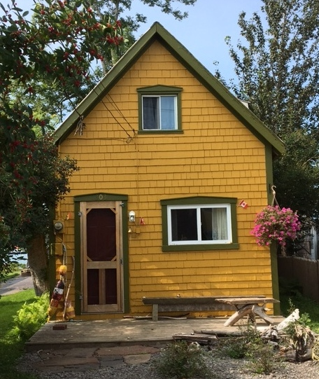 yellow cottage with green tri.