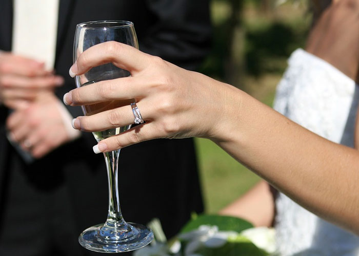 noiva com taça na mão e noivo atrás em segundo plano
