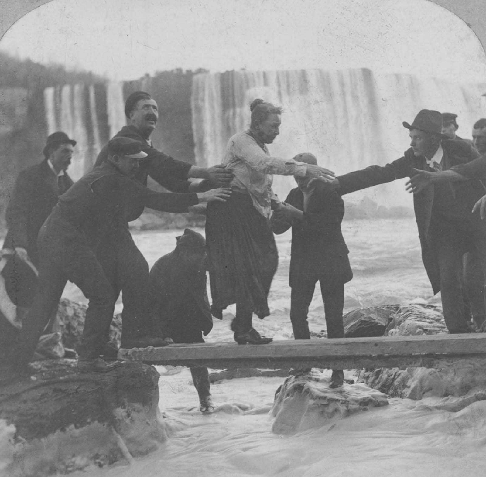 Annie Edson Taylor is helped from the river after becoming the first person to survive a trip over the falls. 1901.
