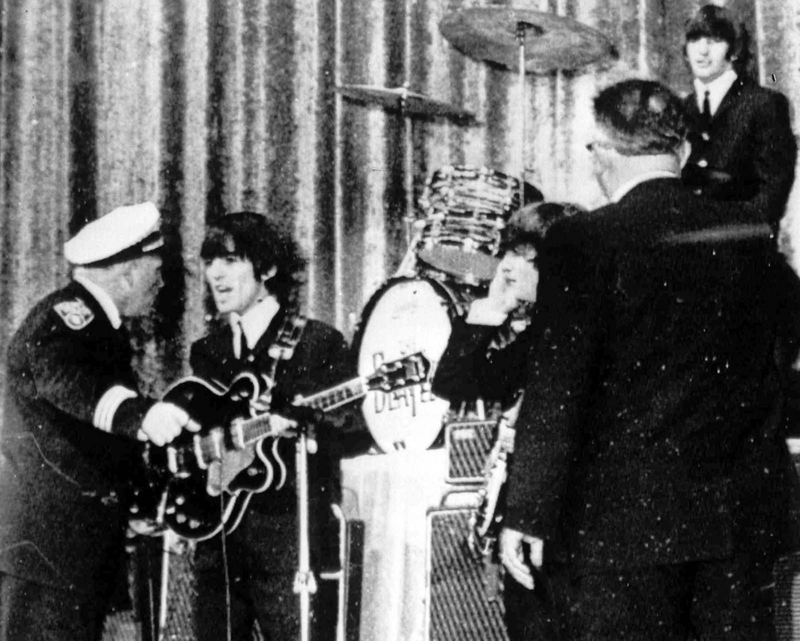 Police Inspector Carl Bear of Cleveland's Juvenile Bureau, left, orders George Harrison and the other members of the Beatles, off the stage of the Public hall, Cleveland, Ohio, on September 16, 1964 as teenagers rushed the stage. Bear let the group back on after wailing youngsters were given 15 minutes to cool down.