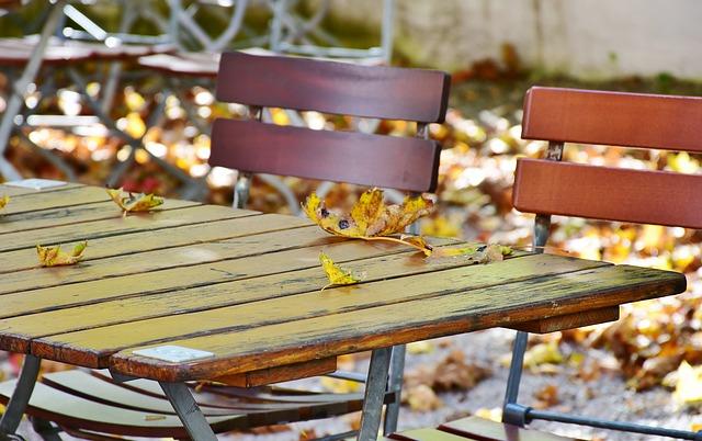 ảnh lá mùa thu rơi xuống bàn ghế
