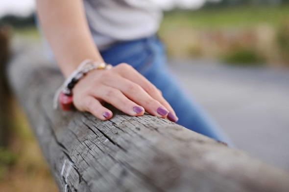 Fotografia di mano di ragazza con smalto viola