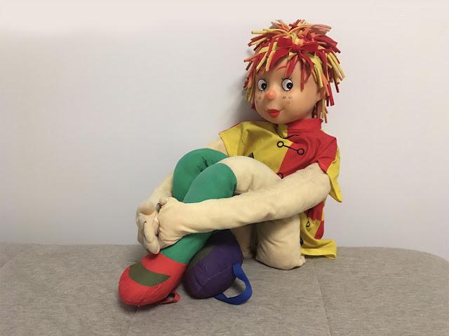 boneca Emília sentada com braços ao redor das pernas