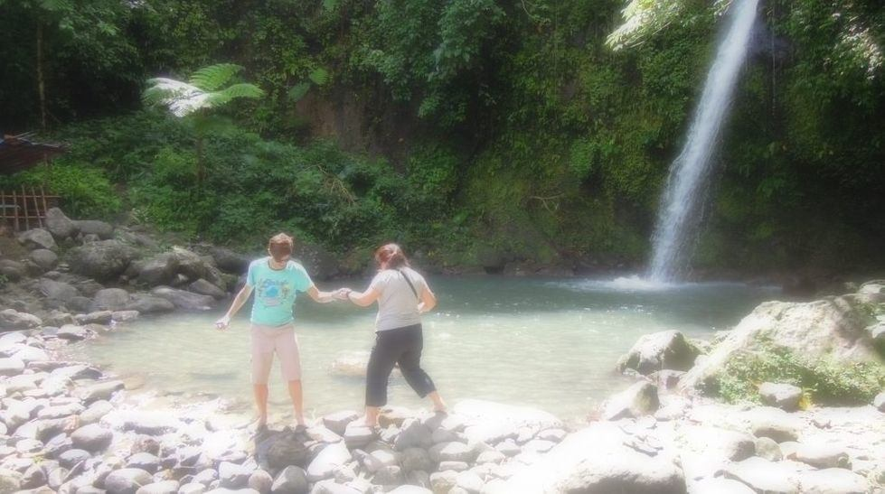 A couple enjoying the water of Vera Falls in Albay