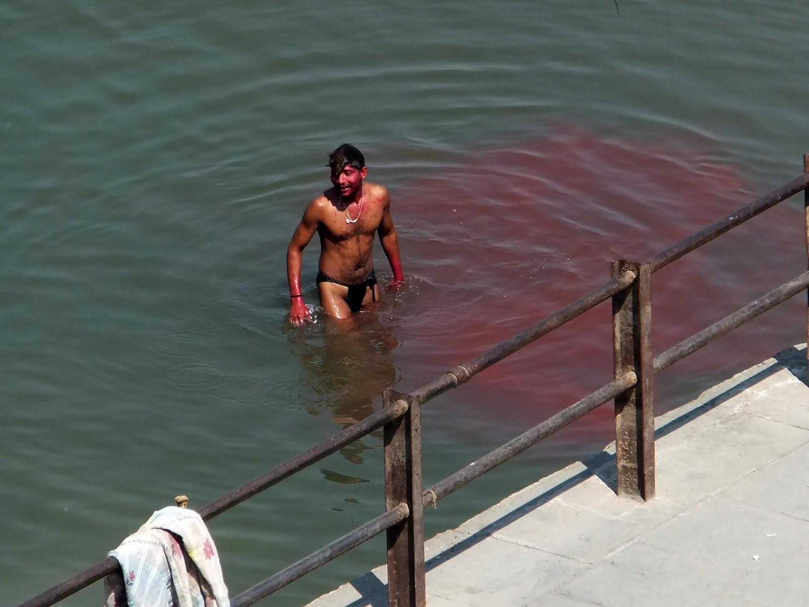 парень в Ганге смывает с себя краску после холи, окрашивая воду вокруг