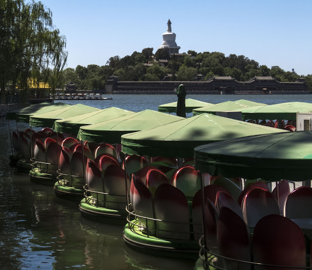 Lotus boats with a view of Beihai Park behind in Beijing