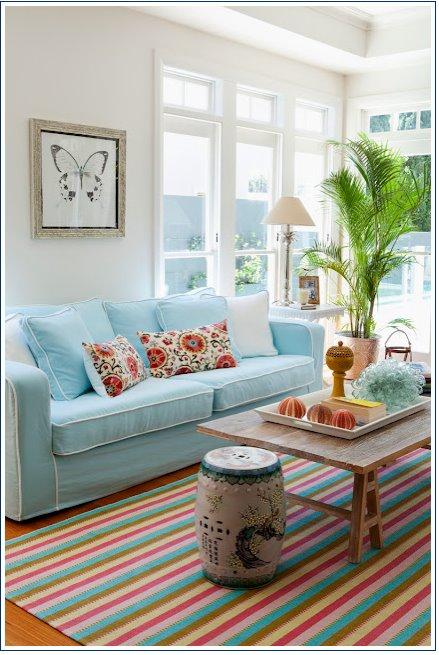 Sala com sofá azul e almofadas coloridas