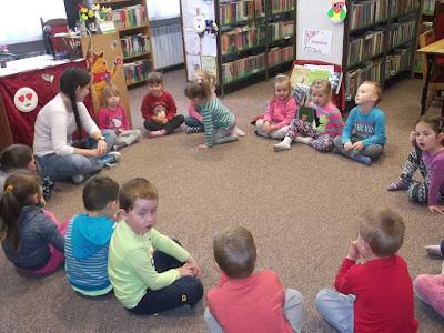 Dzieci siedzą w kole i rozmawiają z bibliotekarką