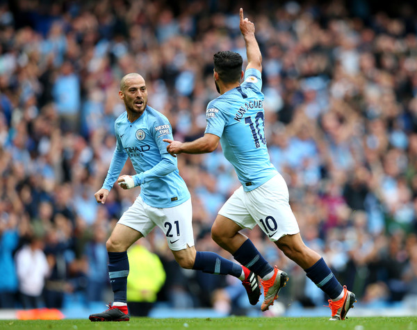 Sergio Aguero of Manchester City celebrates with teammate David Silva after scoring his team's first goal during the Premier League match between Manchester City and Huddersfield Town at Etihad Stadium on August 19, 2018 in Manchester, United Kingdom.