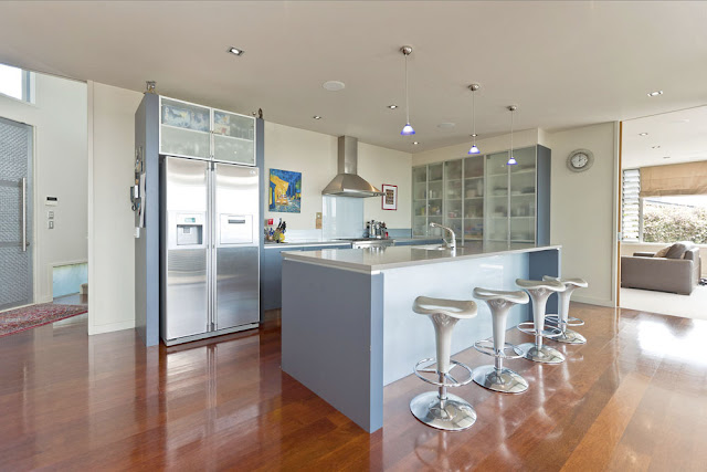 Photo of open kitchen with bar chairs during the day