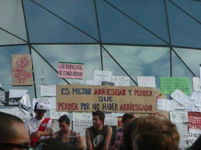 Asamblea del 15M en Sol. Pancarta presidiendo: Es mejor arriesgar y perder que perder por no haber arriesgado.
