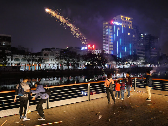 people light fireworks next to the river during the Lunar New Year in Jiangmen