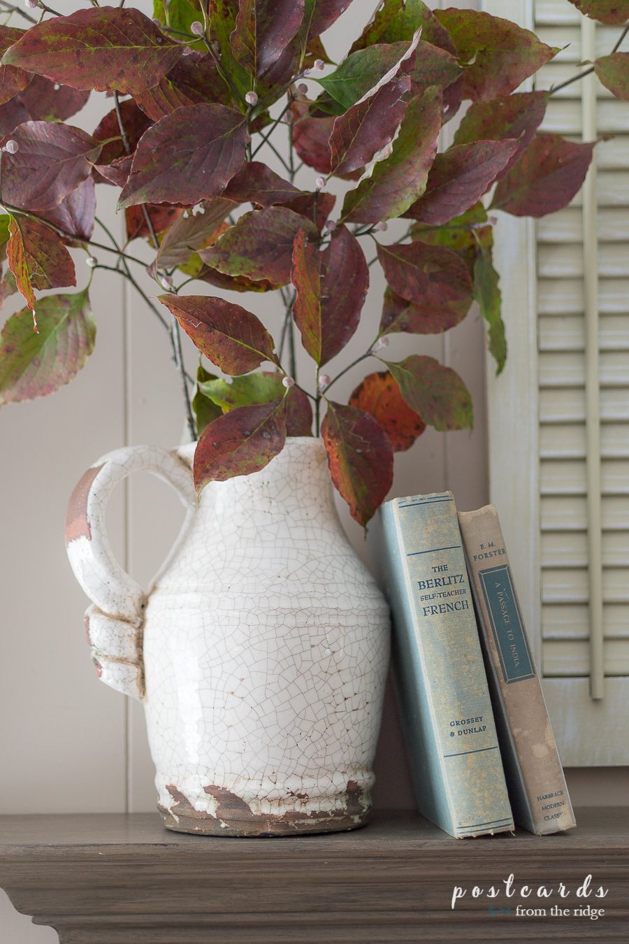 fall dogwood branches in white pitcher with old books on mantel