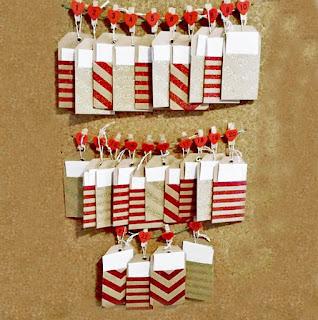 sobres con decoraciones de purpurina colgando de una cuerda sujetos por pinzas rojas numeradas del 1 al 24