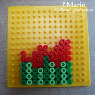 Red and green perler hama beads on a square pegboard