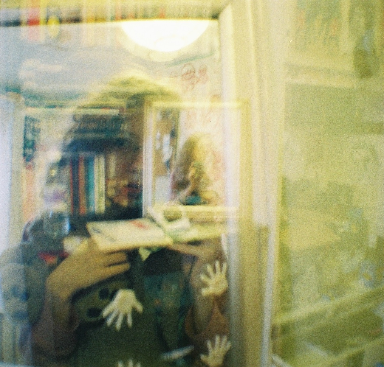 Double exposure showing a young woman appearing twice in a mirror from different distances.