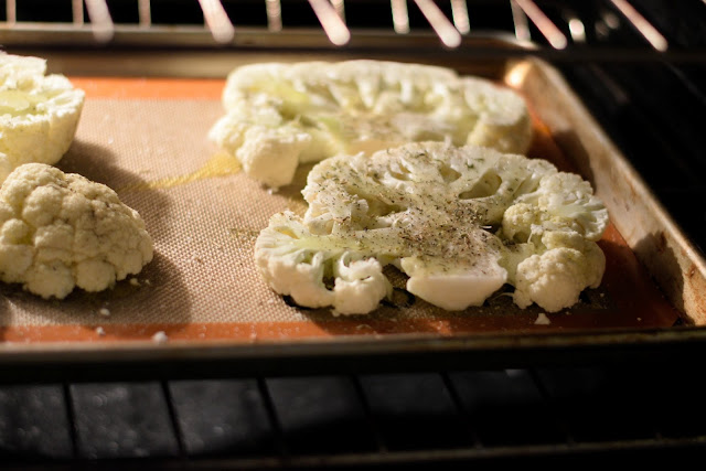 The seasoned cauliflower steaks, on a baking sheet, in the oven.