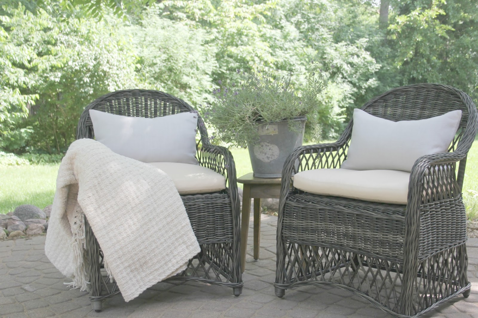 Beautiful dark grey wicker chairs with linen pillows and galvanized bucket of lavender on patio. Hello Lovely Studio.