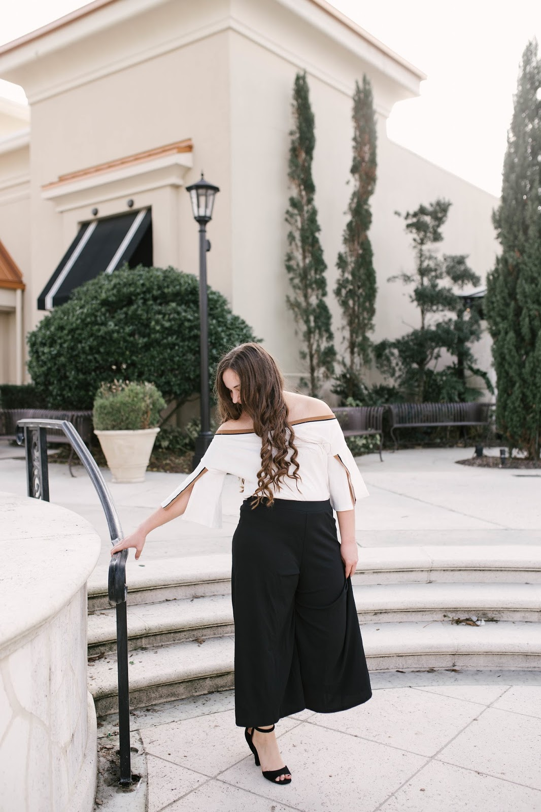 Girl wearing black culotte pants and off the shoulder top