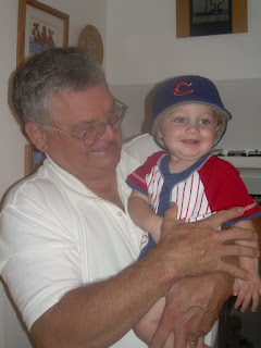 Photo of my dad holding my then one year old son who is wearing Grandpa's Cubs hat