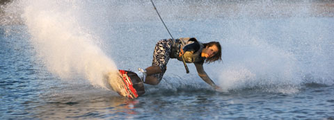 Performance: Close-up of man on wakeboarding reaching down to touch water