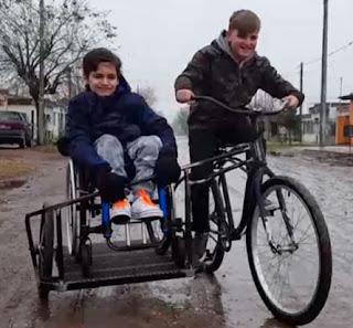 Herrero construyó una bicicleta especial para niño con silla de ruedas y su amigo