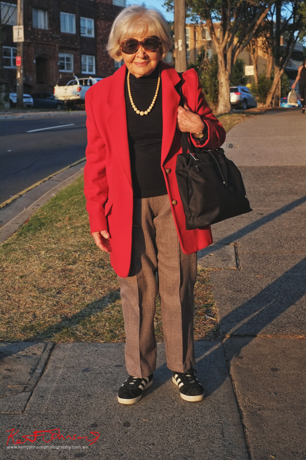 A senior citizen wearin a red winter coat over a black top with pearl necklace, tweedy pants and black Adidas sneakers. Seen on Old South Head Road Bondi Junction. Photographed by Kent Johnson.