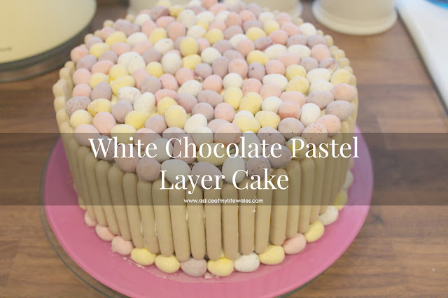white chocolate pastel layer cake with white chocolate finger edging and mini egg topping