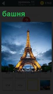 Эйфелевая башня в Париже, вид снизу. Голубое небо с облаками проплывают сверху